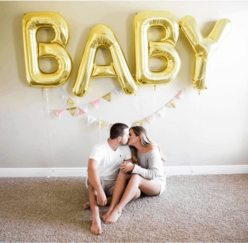 valentine's day pregnancy announcement with big balloons using the letter BABY couple sits on floor kissing with the balloons in the background and they have triangle garland hanging under baby balloons